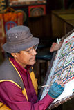 Thangka painting. BHAKTAPUR, NEPAL - SEPTEMBER 22: An unidentified artist creates Thangka painting at local street Festival on September 22, 2011 in Bhaktapur Royalty Free Stock Photography