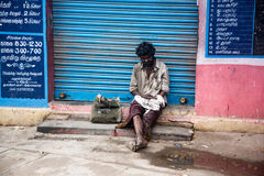 THANJAVUR, INDIA - FEBRUARY 14: Beggar sitting on a street. February 14, 2013 in Thanjavur, India. Poverty in India is widespread, with the nation estimated to Stock Images