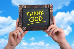 Thank god. A woman holding chalkboard with words thank god on blue sky background Stock Photo
