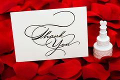 Thank You. A white cakes with a heart on top and thank you card sitting on a red rose petal background, love cakes Stock Photo