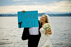 Thank you. A groom is holding up a thank you sign with his bride Stock Photo
