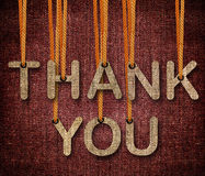 Thank you. Word hunging by rope as puppeteer on sackcloth background stock photo