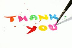 Thank you. Written in vibrant colors as painting with paintbrush on white background stock photo
