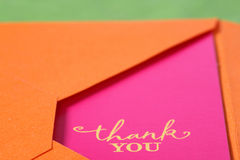 Thank You. Bright pink thank you note with yellow words in an orange envelope Royalty Free Stock Photography