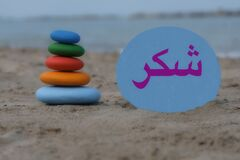 Thank you in arabic language with a creative stones composition on the beach