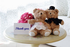 Thank You Bears. A pair of cute bride and groom teddy bears with a thank you note suitable for wedding theme with a bouquet of pink roses at the back Royalty Free Stock Images