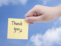 Thank you on blue sky. Single woman hold handwriting word Thank you on note paper with right hand on blue sky background with clipping path Royalty Free Stock Images