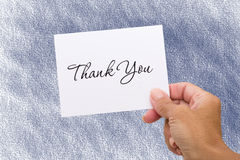 Thank You Card. A hand holding a thank you card on a blue background, thank you card Royalty Free Stock Photography
