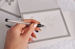 Thank You card. Writing with pen, left handed on silver thank You card Royalty Free Stock Images