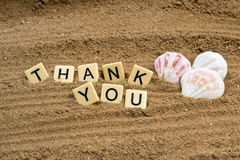 Thank You card. Tile letters in the sand Royalty Free Stock Image