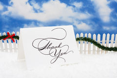 Thank You Card. Sitting on snow with white fence and green garland on a sky background, nutcracker Stock Images