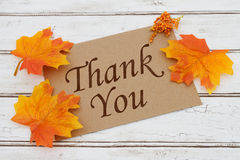 Thank You Card. A brown card with words Thank You over a distressed wood background with Autumn Leaves Royalty Free Stock Photo