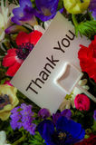 Thank You card in flowers. Close up of bouquet of flowers with message card: Thank You Stock Image