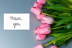 Thank you card, gift box and tulip bouquet on white