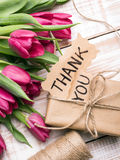 THANK YOU card, gift box and tulip bouquet. On white wooden background Stock Images