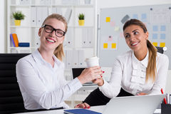 Thank you for the coffee. Smiling women is giving coffee cup to her boss who is taking it gracefully. Concept of bootlicker at work Stock Photos