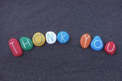Thank you with colored stones design over black volcanic sand