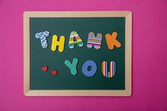 Colorful letters shaping the word thank you on green board with wooden frame, pink wall background. Thank you, Colorful letters shaping the word thank you on royalty free stock images