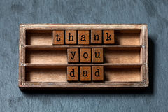 Thank you dad. Father`s day and retro greeting card. Vintage box, wooden cubes phrase with old style letters. Gray stone. Textured background. Close-up, up view Stock Image