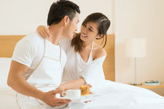 Thank you, dear!. Image of a boyfriend bringing the breakfast in bed to his girlfriend, she hugging him Stock Photography