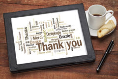 Thank you in different languages. Word cloud on a  digital tablet with a cup of coffee against grunge wood Stock Photo