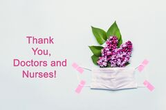Thank You Doctor and Nurses concept with medical mask and lilac flowers