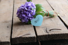 Thank you in French Merci written on tag. Merci written on tag and a bouquet of violets Royalty Free Stock Photos