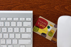 Thank You. Gift card in between keyboard and mouse on a brown wooden grain desktop stock photos