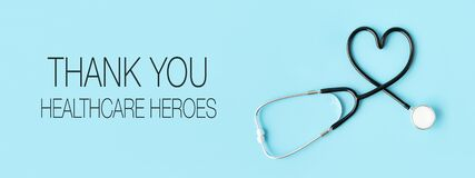 Thank you healthcare heroes message with stethoscope forming a heart on pastel blue background