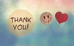 Thank you with heart and smile emoji. Thank you with wooden heart and smile emoji on bokeh light background stock photo
