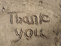 Thank you inscription on wet sand in the sunlight