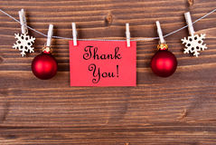 Thank You Label on a Line, Winter Background. Thank You on a Red Label Hanging on a Line with Christmas or Winter Decoration Stock Photography