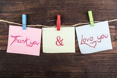 Thank you and love you note. Thank you and love you in sticky notes hanging by clothespin on wood Royalty Free Stock Photo