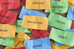 Thank you in many languages. On colorful pieces of paper Stock Photos