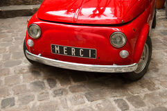 Thank you - Merci - Grazie. A red Italian old car with thank you in French written on the number plate Stock Photo