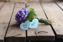 Thank you and Merci written on tag. Merci written on tag and a bouquet of violets Royalty Free Stock Photo