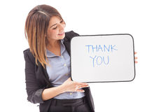 THANK YOU message from a businesswoman. Good looking young brunette in a suit holding a THANK YOU sign on a white background Stock Image