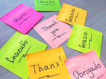 Thank you message on different languages on sticker note on wooden background stock images