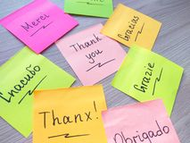 Thank you message on different languages on sticker note on wooden background royalty free stock photography