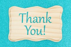 Thank you message on a wood sign. On a teal glitter paper stock image