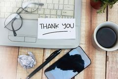 Thank You, Motivational Words Quotes Concept. Thank You words letter, written on piece of memo paper, work desk top view. Motivational business finance royalty free stock images