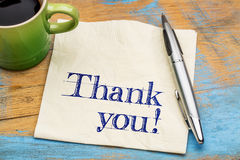 Thank you on napkin. Thank you on a napkin with a cup of coffee against grunge blue painted wood royalty free stock photos