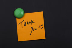 Thank you note on blackboard. Close up of a post-it note saying thank you on blackboard background Stock Photography