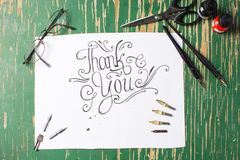 Thank you note calligraphy with writing equipment. On the table Royalty Free Stock Photography