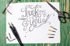 Thank you note calligraphy with writing equipment. On the table Stock Image