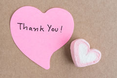 Thank you note in heart shape paper. With valentines candy over brown paper Stock Photography