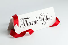 Thank you note. With red ribbon over white background Royalty Free Stock Photo