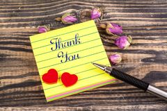 Thank you note. Thank you in sticky note with tow heart and dried rose buds on wood Royalty Free Stock Photography