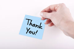 THANK YOU NOTE. Woman hand taping blue adhesive note with Thank You message on white surface Royalty Free Stock Photo