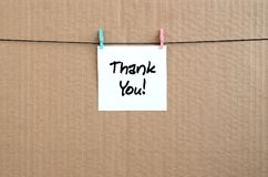 Thank you! Note is written on a white sticker that hangs with a. Clothespin on a rope on a background of brown cardboard stock images